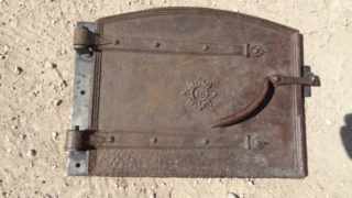 Showing an Old bread oven door with new hinge and catch before the blending finish